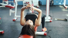 Young sports woman using phone lying on the training apparatus in the gym 20s Stock Footage