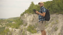 Tourist man He is standing in the mountains, and  using tablet . men with bac Stock Footage