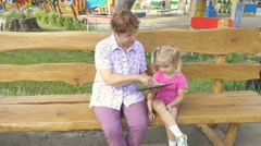 Grandmother Teaching Granddaughter  How to Use a Tablet PC. Sitting on a benc Stock Footage