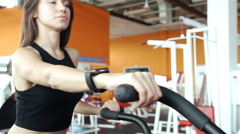 Woman 20s wearing smart watch working out on exercise bike 20s. 1080p Slow Stock Footage
