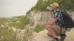 Tourist man close-up sitting the mountain drinks water. men with backpack in Arkistovideo