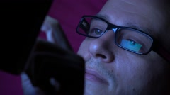 Man in black rim glasses using his tablet computer in dark room. Screen Stock Footage