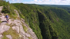 Aerial shot of a man above a tall cliff and a mountain forest Stock Footage