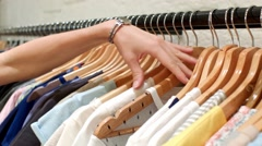 Hand goes through clothes rack Stock Footage