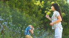 Large woman scolds the small man. Young couple having fight in summer park. A Stock Footage