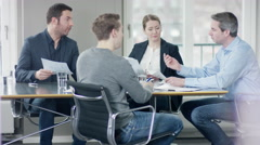 Young men have a job interview with three businesspeople at meetingroom Stock Footage