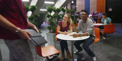 Happy student group working and relaxing together in cafe area of college Stock Footage
