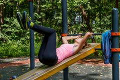 Young slim woman doing workout on training ground Kuvituskuvat