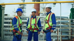 Three workers in production plant as team discussing, industrial scene in Stock Footage