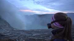 Backpacker female traveler standing at crater rim of Ijen volcano in Indonesia Stock Footage