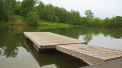 Wooden bridge on bank of a pond Stock Footage