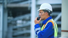 Worker talking on the radio, industrial scene in background Stock Footage