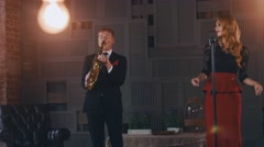 Jazz duet perform on stage. Saxophonist in suit. Vocalist click fingers, dance Stock Footage