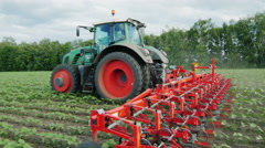 Steadicam shot: Tractor pulls on the field cultivator: which cuts the weeds Stock Footage