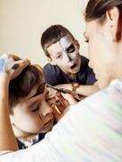 Little cute child making facepaint on birthday party, zombie Apocalypse Stock Photos