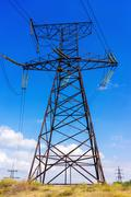 Electricity transmission pylon silhouetted against blue sky. Stock Photos