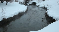 Black stream between snowy banks, dark contaminated water flow over waste land Stock Footage