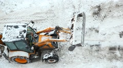 Backhoe loader clean snow from road, top angle view, vehicle scrape asphalt Stock Footage