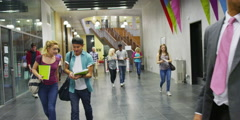 Diverse group of students walking around a large modern university building Stock Footage