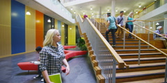 Students walking around a large modern university building Stock Footage