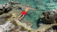 Vacationer in total relaxation floating on crystal clear sea water Stock Footage