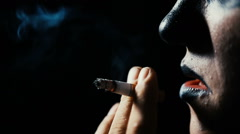 The man smokes a cigarette on a black background. Stock Footage