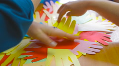 Person counts the number of child finger grips cut from colored paper Stock Footage