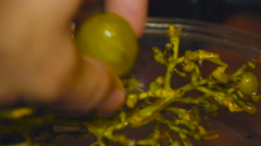 Man breaks the last grape from Grona, lying on a plate Stock Footage