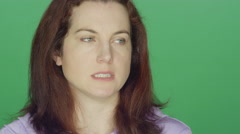Young redhead woman looking worried, on a green screen background Stock Footage