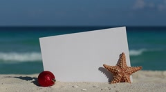 Red fir tree decoration ball and starfish near blank paper board on sandy beach Stock Footage