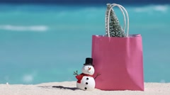 Snowman toy and pink gift paper bag with fir tree at white sandy beach Stock Footage