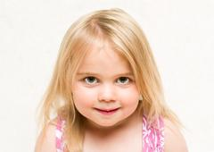 Portrait of beautiful blonde baby girl with cheeky grin Stock Photos