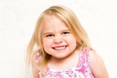Closeup Portrait of Beautiful Toddler Girl Grinning Cheekily Stock Photos