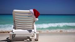 Santa Claus Hat on sunbed near  tropical calm beach Stock Footage