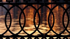 Wrought Iron Fence on the Background of Water at Sunset. Stock Footage