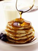 Pouring Maple Syrup Over a Stack of Pancakes Stock Photos