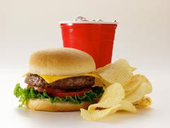 A Cheeseburger with Potato Chips and Soda Stock Photos