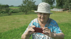 Aged woman taking photos the nature of park Stock Footage