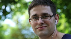 Man with earphones looks at the camera Stock Footage