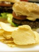 Potato Chips with Hamburger in the Background Stock Photos
