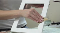 Girl cleans sandpaper handmade frame Stock Footage