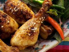 Asian chicken legs with sesame and chili peppers Stock Photos