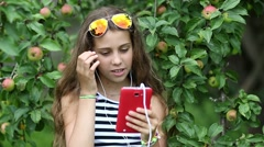 Beautiful girl stands near apple tree and speaks on red smartphone Stock Footage