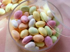 Pastel-coloured sugar eggs (jelly beans) in acrylic box Stock Photos
