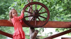 Little girls turn wooden wheel Stock Footage