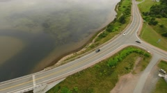 Aerial shot of car driving over a bridge above river Stock Footage
