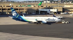 Alaska airlines plane, airport tow tug Stock Footage