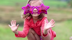 Funny little girl in big glasses in the shape of stars looks at the camera Stock Footage