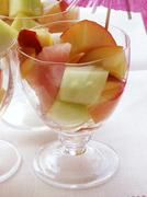 Colourful fruit salad with melon in glasses with parasol Stock Photos