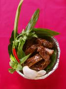 Crispy spare-ribs with herbs and krupuk in aluminium dish Stock Photos